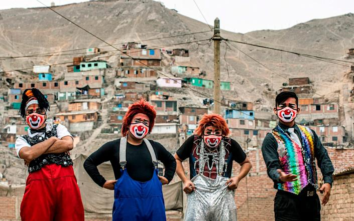 Clowns wearing face masks pose for a picture before performing - AFP