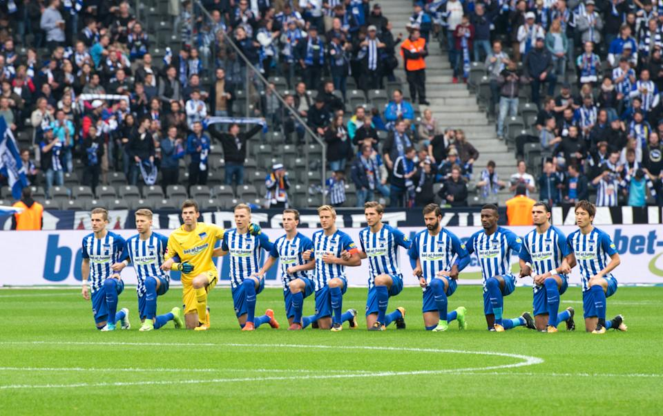 Hertha's players kneeling with linked arms in collective protest against discrimination during the German Bundesliga soccer match between Hertha BSC and FC Schalke 04 in Berlin, Germany, 14 October 2017. (Photo by Annegret Hilse/picture alliance via Getty Images)