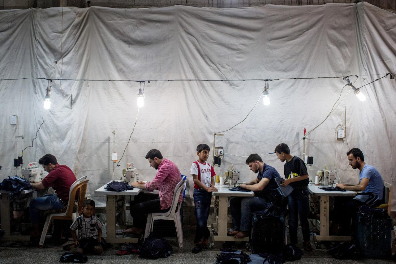 <p>Syrian refugees work in a Syrian-owned clothing factory on May 17, 2016, in Gaziantep, Turkey. Turkey's massive and largely unregulated garment industry is an attractive option for Syrian refugees to work both legally and illegally despite low wages, long hours and poor conditions. It is a popular choice for Syrians living outside of the official refugee camps, who are offered no assistance from the state. (Chris McGrath/Getty Images) </p>