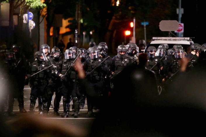 Portland police clash with protesters during a demonstration in downtown Portland, early Thursday, Aug. 13, 2020. The demonstration lasted into the predawn hours of Thursday, with some in the crowd setting a fire and exploding commercial grade fireworks outside a federal courthouse that's been a target in months of conflict for Oregon's largest city. (Sean Meagher/The Oregonian via AP)