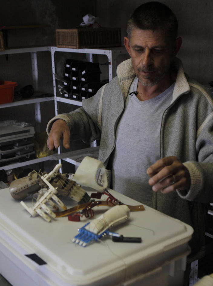 In this photo taken Tuesday, Aug. 20, 2013 in Johannesburg Robohand inventor Richard van As, shows hands that he has made for people in his workshop at his home. Van As, who lost four fingers to a circular saw two years ago decided to build his own hand after seeing a video posted online of a mechanical hand made for a costume in a theater production by designer Ivan Owen in Seattle USA. Van As and Owen invented the Robohand that uses cables, 3D printing, screws and thermoplastic and has fitted about 170 people with robohands. (AP Photo/Denis Farrell)