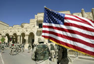 FILE - In this March 16, 2004, file photo, a U.S. soldier from the 1st Infantry Division walks with a U.S. flag after the changeover ceremony in one of ousted Iraqi President Saddam Hussein's palaces, now a U.S. army base, in Tikrit, about 110 miles (180 kilometers) northwest of Baghdad, Iraq. In Iraq, a country that still struggles with the controversial legacy of a U.S.-led invasion in the name of democracy, many people followed the Washington events with a mixture of shock and fascination. (AP Photo /Murad Sezer, File)
