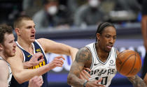 San Antonio Spurs forward DeMar DeRozan, right, fights for control of the ball with Spurs center Jakob Poeltl, left, and Denver Nuggets center Nikola Jokic, center, in the second half of an NBA basketball game Friday, April 9, 2021, in Denver. (AP Photo/David Zalubowski)