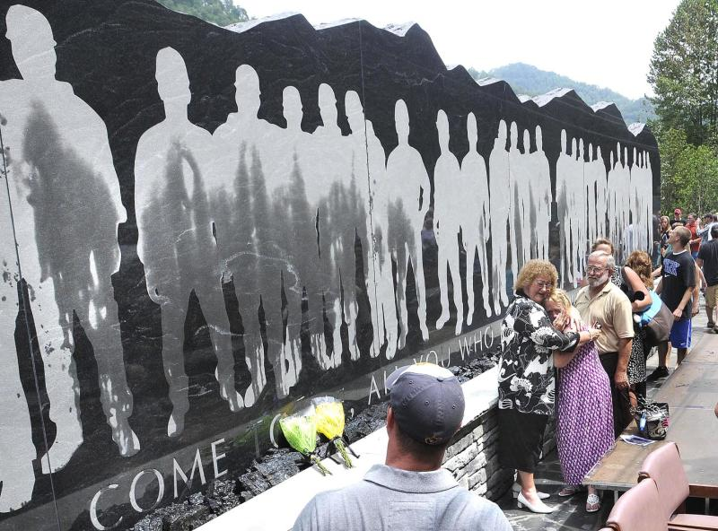 Family and friends view the 48-foot-long granite Upper Big Branch Miners monument, Friday, July 27, 2012 in Whitesville, W.Va,  On the heels of a West Virginia coal mining death, families of the 29 men killed in the Upper Big Branch mine dedicated a memorial Friday to their fallen relatives and those injured in the April 2010 explosion. (AP Photo/The Register-Herald, Rick Barbero)