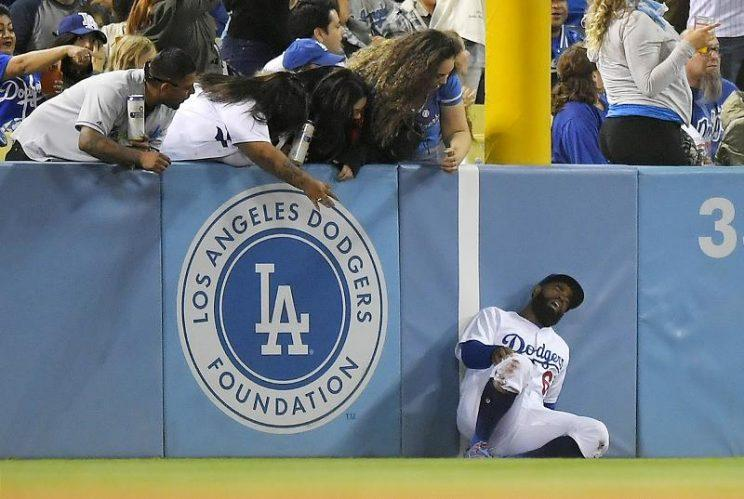 Dodgers left fielder Andrew Toles writhes after running into the left field wall while trying to catch a ball hit during Tuesday's game at Dodger Stadium. (AP)