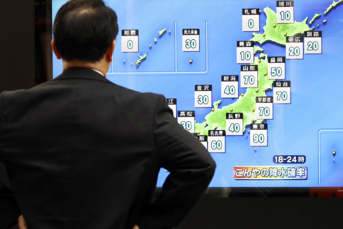 A man watches a public TV of weather forecast in Tokyo Friday, Oct. 11, 2019. Japan's weather agency is warning a powerful typhoon may bring torrential rains to central Japan over the weekend. (AP Photo/Eugene Hoshiko)