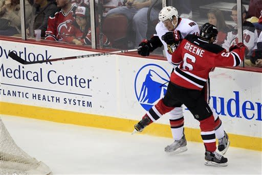 New Jersey Devils' Andy Greene (6) checks Ottawa Senators' Colin Greening (14) during the second period of an NHL hockey game in Newark, N.J., Saturday, April 7, 2012. (AP Photo/Mel Evans)