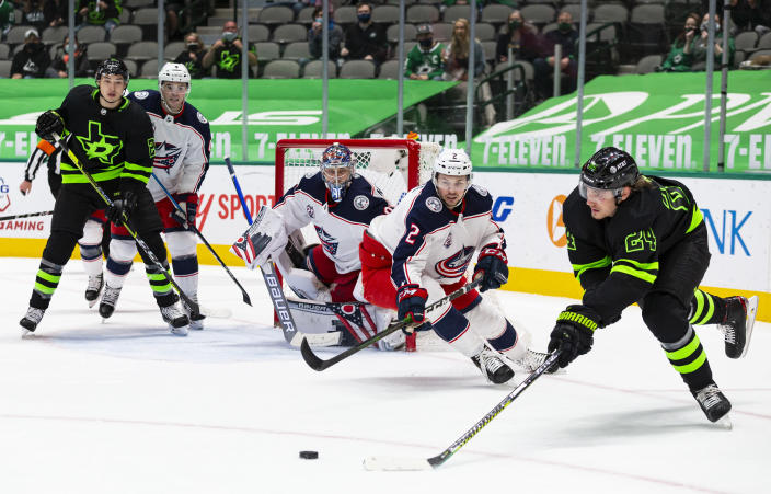 Dallas Stars left wing Roope Hintz (24) skates for the puck as Columbus Blue Jackets defenseman Andrew Peeke (2) pursues during the second period of an NHL hockey game Saturday, April 17, 2021, in Dallas. (AP Photo/Sam Hodde)