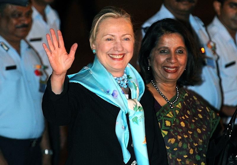 US Secretary of State Hillary Rodham Clinton, left, gestures to the media,  flanked by Indian Foreign Secretary Nirupama Rao, right, upon her arrival at Air Force station,  in New Delhi, Monday, July 18, 2011. U.S. Secretary of State Hillary Rodham Clinton arrived in India for security and counterterrorism talks as the two countries try to broaden their relationship. (AP Photo/Prakash Singh, Pool)