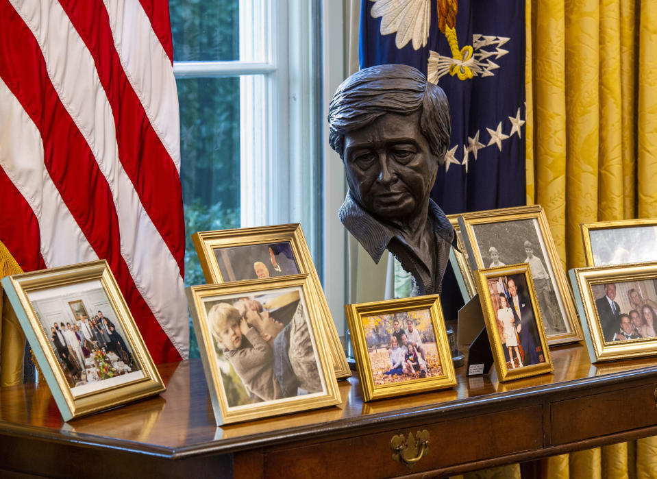 A sculpted bust of Cesar Chavez oversees a collection of personal framed photos on a table in the Oval Office awaiting President Joseph Biden at the White House in Washington, DC. / Credit: Bill O'Leary/The Washington Post via Getty Images