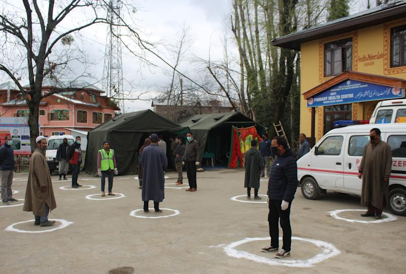 People stand in designated area to maintain social distance as they queue up outside a Government Hospital at Baramulla in North of Srinagar, Indian administered Kashmir in India. Source: Sipa USA
