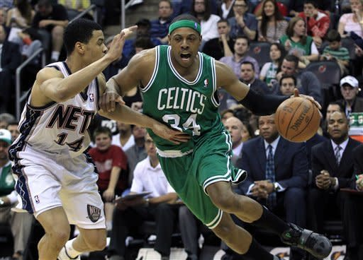 Boston Celtics' Paul Pierce (34) dribbles the ball as New Jersey Nets' Gerald Green (14) tries to block his path during the second quarter of an NBA basketball game in Newark, N.J., Saturday, April 14, 2012. (AP Photo/Mel Evans)