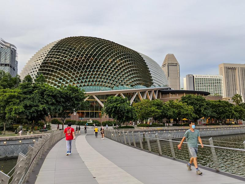May 2020. Singapore. Scene of everyday Singapore during the world pandemic of 2020 Coronavirus / COVID - 19 people walking with masks one and exercising while a architectural marvel stands in the background (The Esplanade Theater) aka the Durian. Man is seen walking near camera while wearing a mask