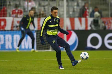 Arsenal's Mesut Ozil warms up before the match