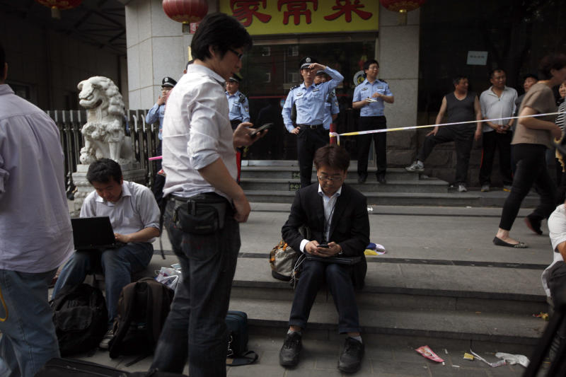Chinese police officers watch over journalists outside the hospital where blind Chinese activist Chen Guangcheng is recuperating in Beijing, China, Thursday, May 3, 2012. U.S. officials said Thursday they are still trying to help Chen who says he fears for his family's safety, and denied he was pressured to leave the American Embassy to resettle inside China.(AP Photo/Ng Han Guan)