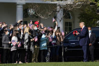 President Donald Trump gives out hats to supporters as he departs the South Lawn of the White House, Saturday, Oct. 31, 2020, in Washington. (AP Photo/Alex Brandon)