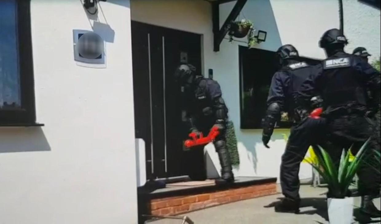 National Crime Agency officers conducting a raid on a property in Croydon (National Crime Agency/PA)