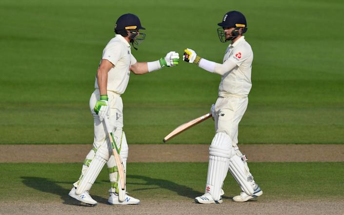 England's Jos Buttler, left, and Chris Woakes fist bump during the fourth day of the first cricket Test match between England and Pakistan - Getty Pool
