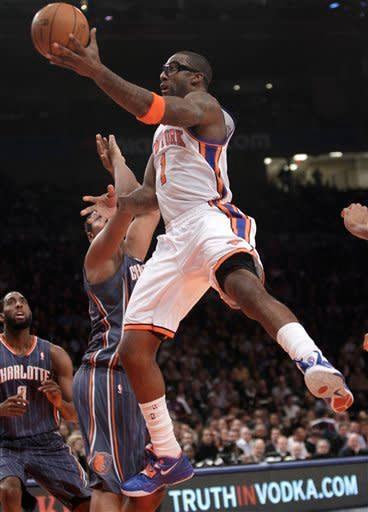 New York Knicks forward Amare Stoudemire (1) goes up over Charlotte Bobcats forward Boris Diaw (32) as Bobcats forward D.J. White watches from the floor in the first half of an NBA basketball game at Madison Square Garden in New York, Monday, Jan. 9, 2012. (AP Photo/Kathy Willens)