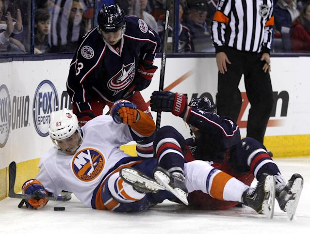 New York Islanders' Anders Lee (27), Columbus Blue Jackets' Cam Atkinson (13) and Artem Anisimov (42), of Russia, work for the puck in the second period of an NHL hockey game in Columbus, Ohio, Sunday, April 6, 2014. (AP Photo/Paul Vernon)