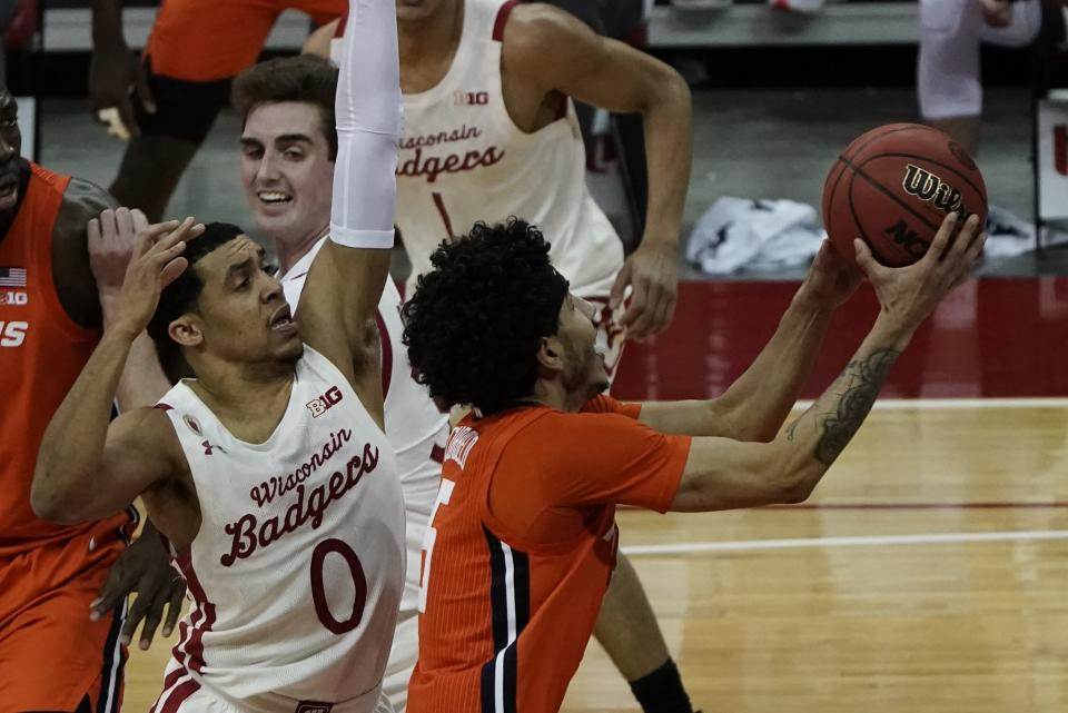 Illinois's Andre Curbelo drives past Wisconsin's D'Mitrik Trice during the first half of an NCAA college basketball game Saturday, Feb. 27, 2021, in Madison, Wis. (AP Photo/Morry Gash)