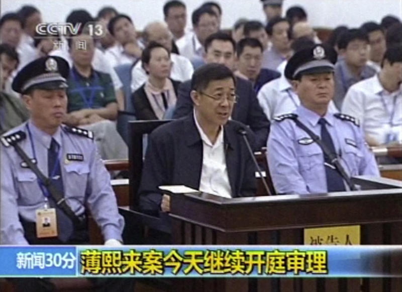 In this image taken from video, former Chinese politician Bo Xilai, center, addresses a court at Jinan Intermediate People's Court in eastern China's Shandong province, Saturday, Aug. 24, 2013. Disgraced politician Bo on Saturday mocked a former city official's testimony that he embezzled government funds with a phone call to his wife, refuting the latest allegation in a politically charged trial that's laid bare tales of greed, machinations and betrayal in one of China's elite families. The superimposed letters read: Bo Xilai case continues with open court trial. (AP Photo/CCTV via AP Video) CHINA OUT, TV OUT
