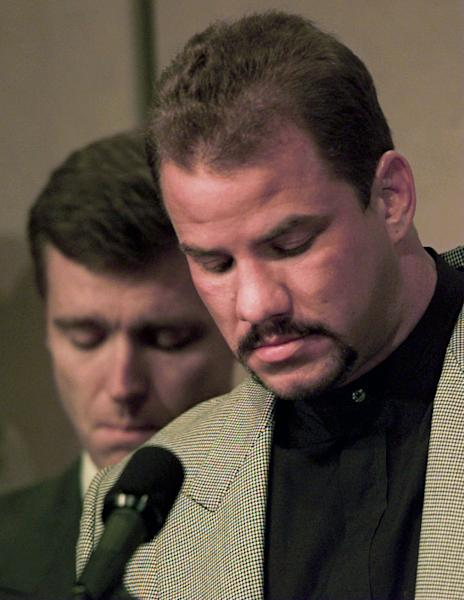 """FILE - In this Feb. 15, 1996 file photo, heavyweight boxer Tommy Morrison, right, and promoter Tony Holden bow their heads during an emotional moment at a news conference about Morrison being HIV positive, in Tulsa, Okla. Morrison, a former heavyweight champion who gained fame for his role in the movie """"Rocky V,"""" has died. He was 44. Holden says his longtime friend died Sunday night, Sept. 1, 2013, at a Nebraska hospital. (AP Photo/David Longstreath, File)"""