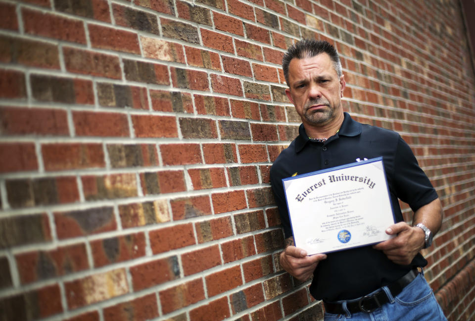In this March 11, 2016 photo, Shane Satterfield, a roofer who owes more than $30,000 in debt for an associate's degree in computer science from one of the country's largest for-profit college companies that failed in 2014, holds his diploma in Atlanta.