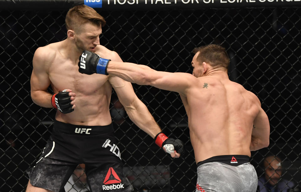 Michael Chandler punches Dan Hooker of New Zealand in a lightweight fight during the UFC 257 event.