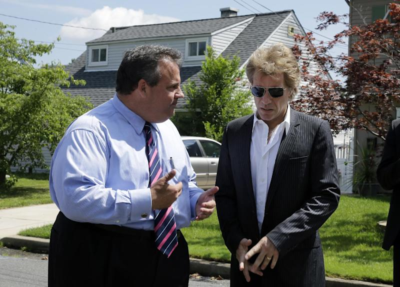Singer Jon Bon Jovi, right, listens to New Jersey Gov. Chris Christie Monday, July 8, 2013, as they walk in Sayreville, N.J. Bon Jovi is giving $1 million to help the band's home state recover from Superstorm Sandy. Bon Jovi has been a high-profile presence in his hometown since some neighborhoods were wiped out by Sandy last year. The singer says he wants to do what he can to help, including telling the world about the central New Jersey community's struggles. (AP Photo/Mel Evans,Pool)