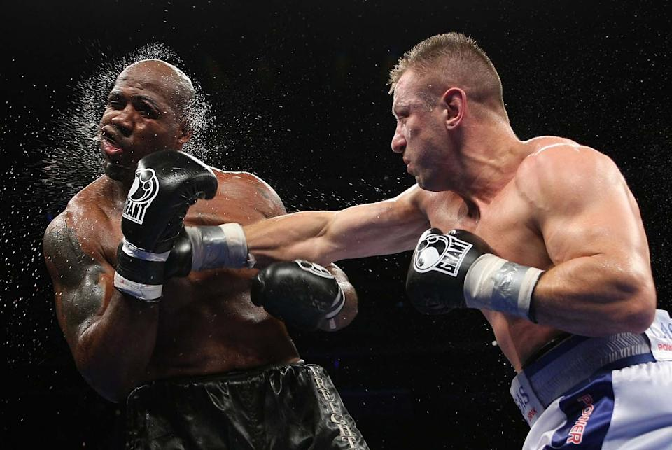 Tomasz Adamek, right, of Poland, lands a punch on Travis Walker during the fifth round of a heavyweight boxing match at the Prudential Center in Newark, N.J., Saturday, Sept. 8, 2012. Adamek won by TKO in five rounds. (AP Photo/Tim Larsen)