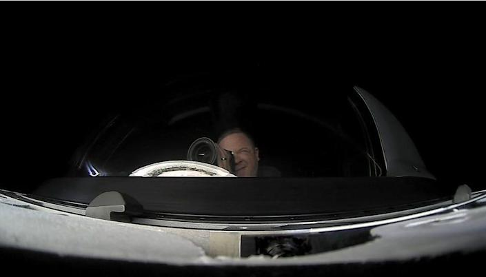 Inspiration4 crew member Chris Sembroksi looking through a telescope aboard as he orbits the Earth in a SpaceX Crew Dragon capsule.