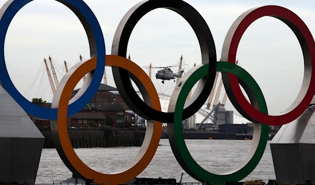 A Royal Navy helicopter passes Olympic rings installed on The River Thames at Greenwich on August 1, 2012 in Greenwich, England. (Photo by Peter Macdiarmid/Getty Images)
