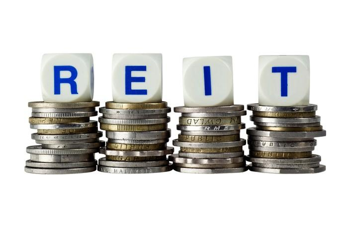 The acronym REIT spelled out with dice atop piles of coins.