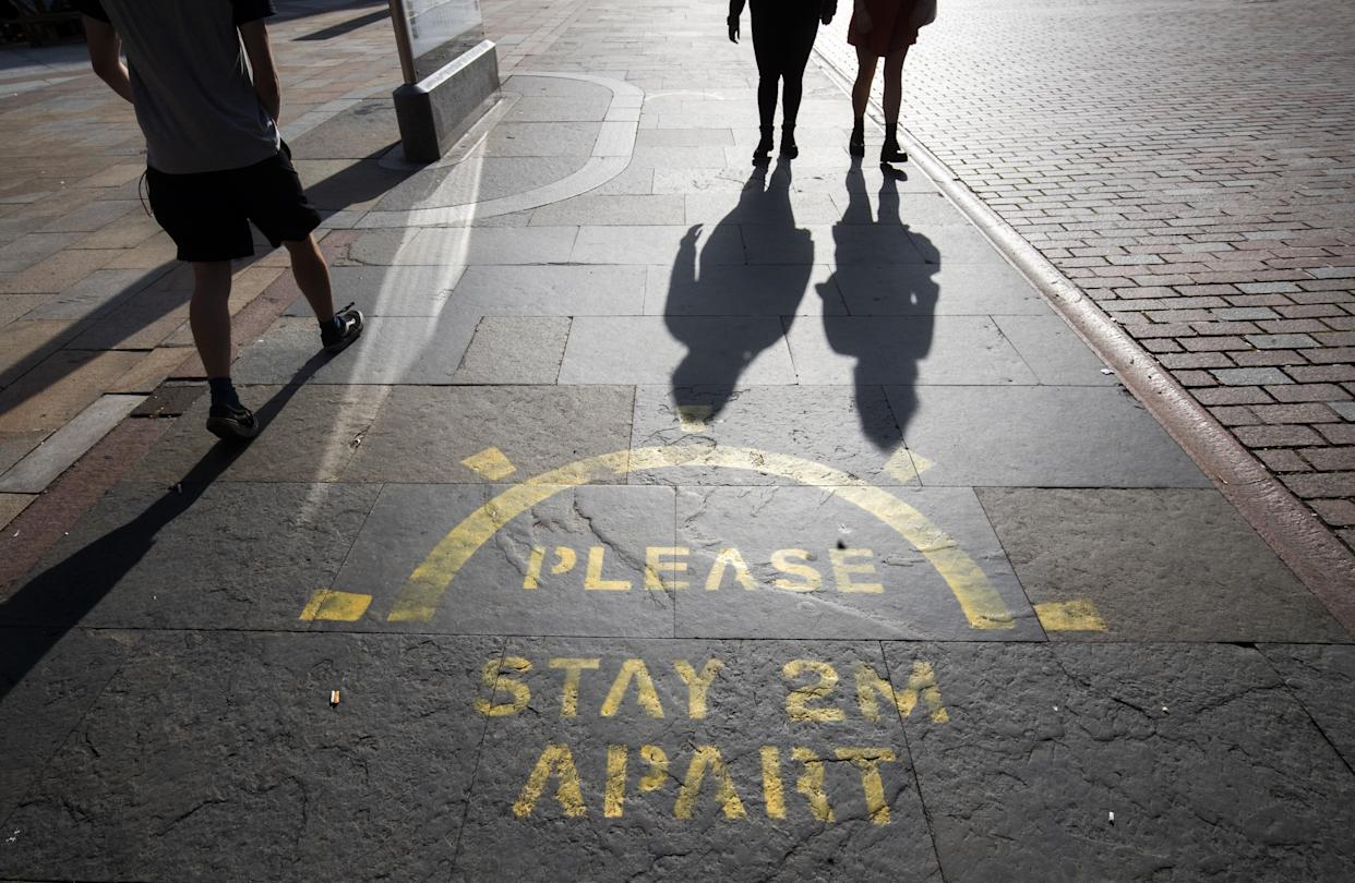The changing face of the high street. People cast shadows walking past a social distancing information sign painted on the pavement on the high street in Dundee in Scotland, some six months on from the evening of March 23 when Prime Minister Boris Johnson announced nationwide restrictions. (Photo by Jane Barlow/PA Images via Getty Images)