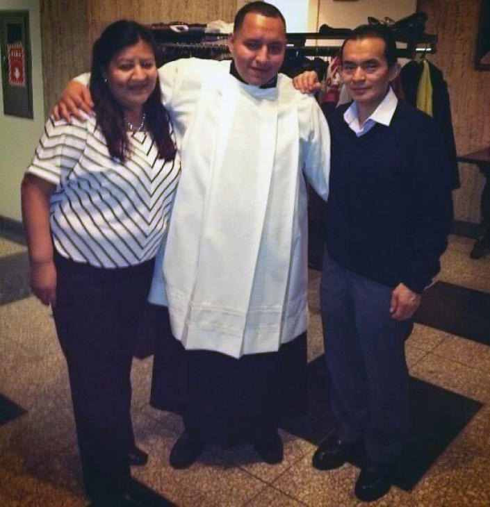 In this December 2014 handout provided by Rev. Joseph Dutan, Dutan poses with his mother, Ana, and father, Manuel at seminary in the Queens borough of New York. Rev. Joseph Dutan recently lost his father, Manuel Dutan, to coronavirus. (Courtesy of Joseph Dutan via AP)