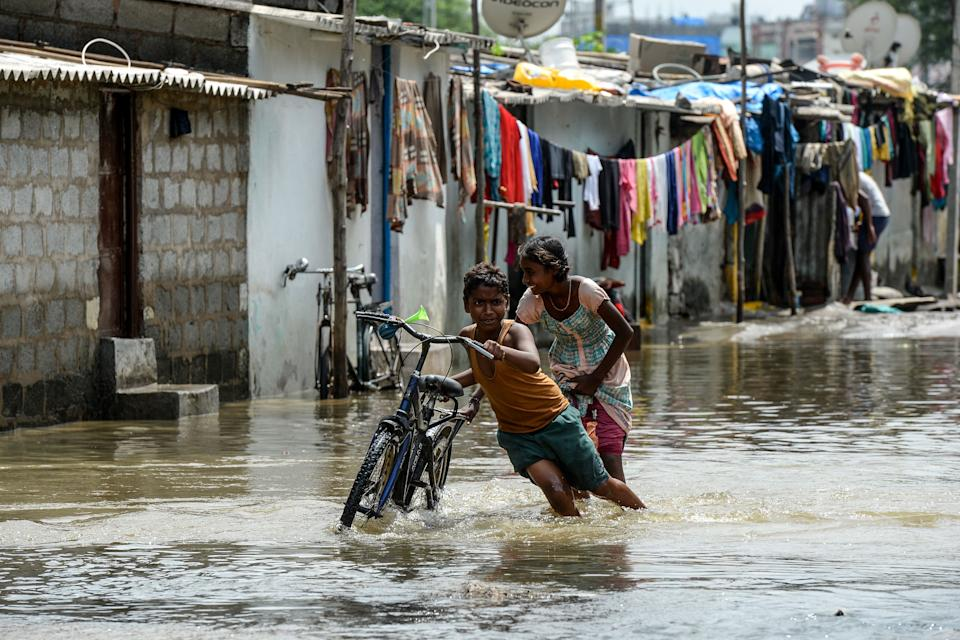 TOPSHOT - Children push a bicycle making their way on a flooded street following heavy rains in Hyderabad on October 15, 2020. (Photo by NOAH SEELAM / AFP) (Photo by NOAH SEELAM/AFP via Getty Images)