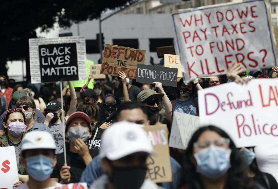 Protesters carry defund police signs.