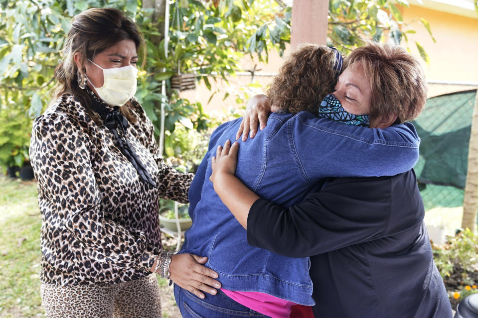 Elvira Carvajal, right, hugs Blanca Flores, as Irma Durand, left, cries after watching the swearing-in ceremony for Joe Biden as the 46th President of the United States, Wednesday, Jan. 20, 2021, in Homestead, Fla. Immigrants cheered President Joe Biden's plan to provide 11 million people without legal U.S. status a path to citizenship, on Wednesday mixing hope with guarded optimism amid a seismic shift in how the American government views and treats them. (AP Photo/Marta Lavandier)