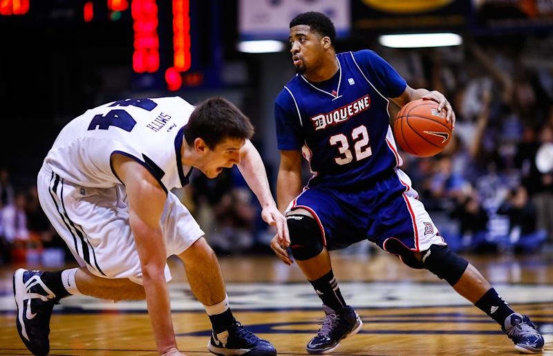 INDIANAPOLIS, IN - FEBRUARY 19: As Andrew Smith #44 of the Butler Bulldogs stumbles Sean Johnson #32 of the Duquesne Dukes dribbles the ball up court at Hinkle Fieldhouse on February 19, 2013 in Indianapolis, Indiana. Butler defeated Duquesne 68-49. (Photo by Michael Hickey/Getty Images)