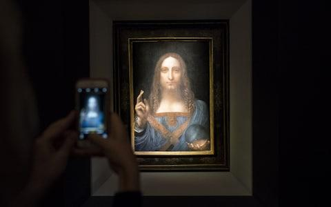 A visitor takes a photo of the painting 'Salvator Mundi' by Leonardo da Vinci at Christie's New York Auction House, November 15, 2017 in New York City. - Credit: Drew Angerer/Getty Images North America