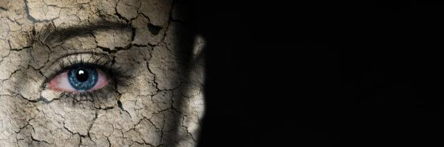 Woman's face covered with cracked earth texture.