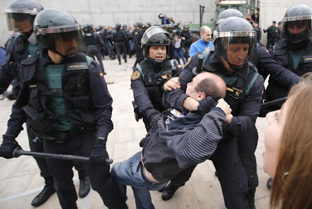 <p>Spanish Guardia Civil guards drag a man outside a polling station in Sant Julia de Ramis, where Catalan president was supposed to vote, on Oct. 1, 2017, on the day of a referendum on independence for Catalonia banned by Madrid. (Photo: Fabio Bucciarelli/AFP/Getty Images) </p>