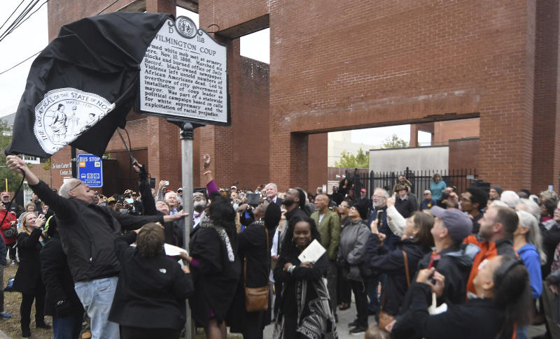 The new North Carolina highway historical marker to the 1898 Wilmington Coup is unveiled during a dedication ceremony in Wilmington, N.C., Friday, Nov. 8, 2019. The marker stands outside the Wilmington Light Infantry building, the location where in 1898, white Democrats violently overthrew the fusion government of legitimately elected blacks and white Republicans in Wilmington. (Matt Born/The Star-News via AP)