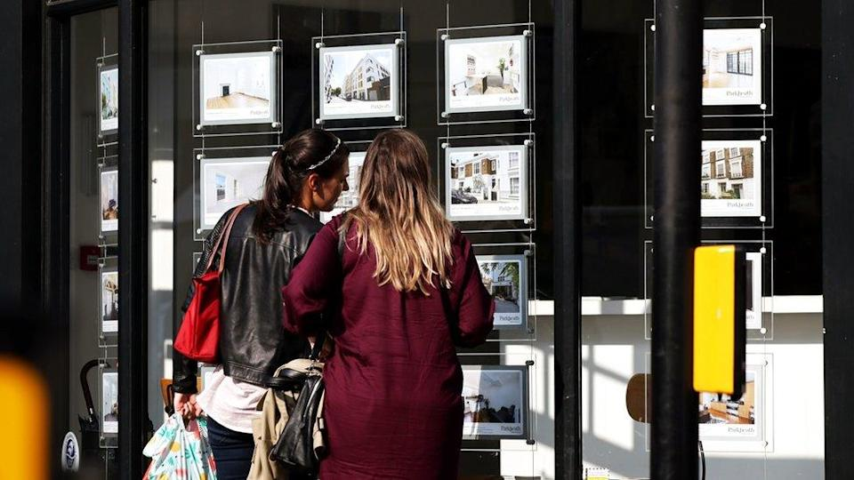 Two women look at houses in an estate agent's window