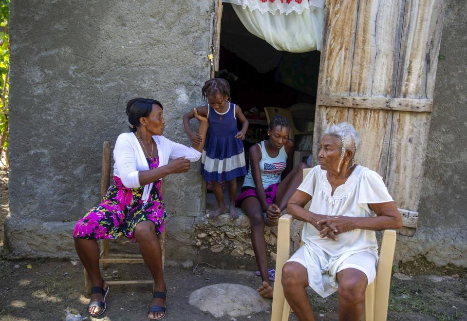 Naffetalie Paul, 8, is helped by her Aunt Lizette Paul from the doorway where her cousin Lovenyda Paul sits near her great-grandmother Dieumene Bastien, who lost her son Fritznel Paul, Naffetalie's father, to cholera 13 years ago in Mirebalais, Haiti, Monday, Oct. 19, 2020. Ten years after a cholera epidemic swept through Haiti and killed thousands, families of victims still struggle financially and await compensation from the United Nations as many continue to drink from and bathe in a river that became ground zero for the waterborne disease. (AP Photo/Dieu Nalio Chery)