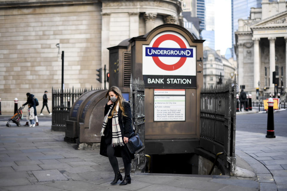 A woman wears a face mask as she steps out of Bank underground station, in London. Photo: Alberto Pezzali/AP