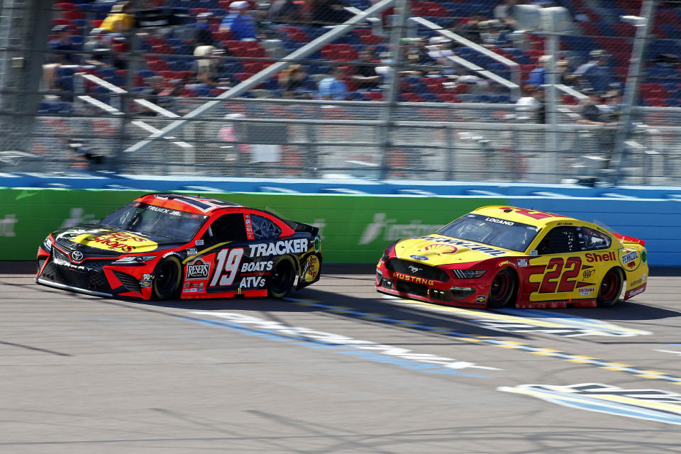 Martin Truex Jr (19) and Joey Logano (22) race through Turn 4 during a NASCAR Cup Series auto race at Phoenix Raceway, Sunday, March 14, 2021, in Avondale, Ariz. (AP Photo/Ralph Freso)
