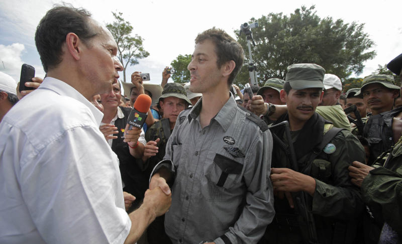 French diplomat Jean-Baptiste Chauvin, left, shakes hands with freed French journalist Romeo Langlois after Langlois' release by rebels in San Isidro in southern Colombia, Wednesday, May 30, 2012. Langlois, who was taken by rebels of the Revolutionary Armed Forces of Colombia (FARC) on April 28 when they attacked troops he was accompanying on a cocaine-lab eradication mission, was handed over by the rebels to a delegation that included the French diplomat. (AP Photo/Fernando Vergara)