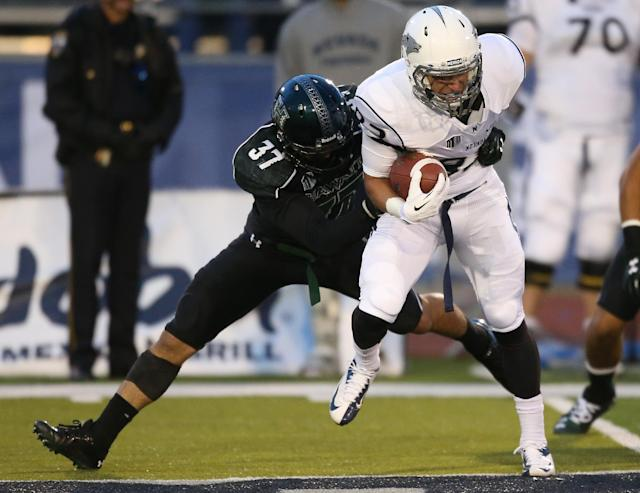 Nevada's Joseph Huber (83) fights to break free from Hawaii's Charles Clay (37) during the second half of an NCAA college football game in Reno, Nev., on Saturday, Sept. 21, 2013. (AP Photo/Cathleen Allison)